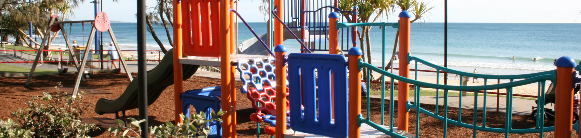 Colourful playground with a pathway and Mooloolaba beach in background