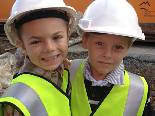 Children wearing hard hats and hi-vis vests on a construction site